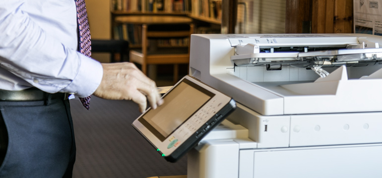 Photograph of a man using a photocopier. used as a header image for a blog about GDPR and print management software PaperCut